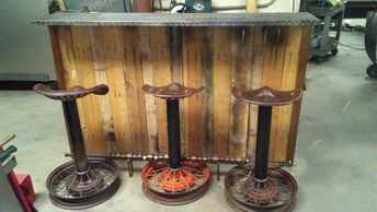 Bar and Barstools. Bar is built from Pallet wood, Rebar, and Diamond plate stainless steel. Barstools are made from tractor seats, Pipe and Motorcycle rims