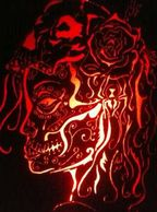 Hand Cut from Steel Profile Image of a Woman with Face Decorated to Celebrate Day of the Dead, Wearing a Skull and Rose on her head, Back lit with red lights