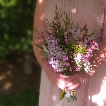 Bride or bridesmaid holding wild, purple and green, spring bouquet. Lilac, campion and grasses