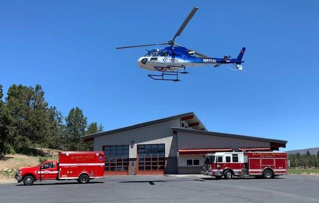 Station 5 with an ambulance and engine parked in front with a helicopter hovering over them.