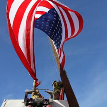 Firefighter changing the flag displayed in the Town and Country Shopping Center
