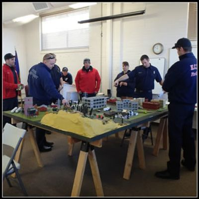 crews standing around a mock city during a tabletop exercise.