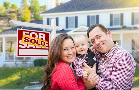 Happy family outside house with sold sign sold their house with Janiene Palmeri.