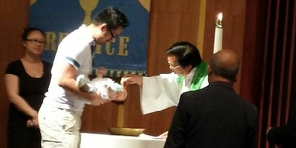 Rev. Faivneng Her conducts a Baptism at Hmong Hope Lutheran Church in Milwaukee, Wisconsin