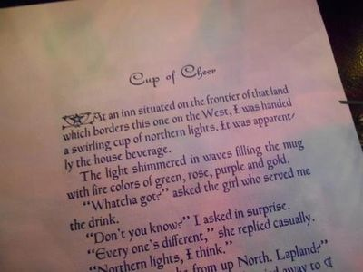 This page from Winter Tales displayed under Christmas lights. Light plays a role in Cup of Cheer.