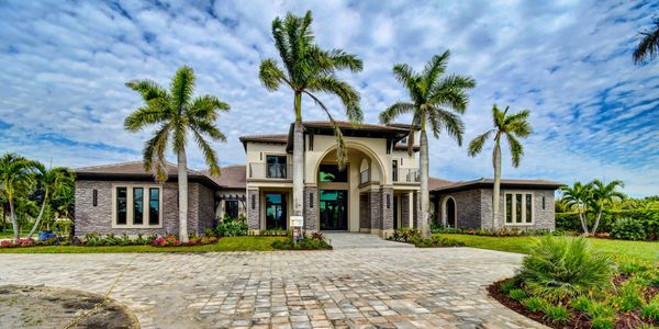 Large, luxurious mediterranean style home with stone front, large circular driveway and palm trees