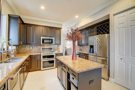 Kitchen picture with granite countertops, stainless steel appliances, dark cabinetry and wine rack
