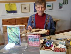 Katherine Colwell working in her studio with 2-sided and framed embroidery for sale.
