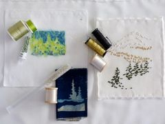 Conifers in three media, by Katherine Colwell, and embroidery plan options, thread spools, beads.