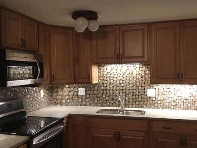 New cabinet installation with custom backsplash and granite countertops