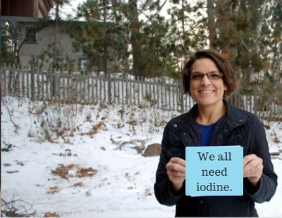 "A picture of hyperthyroidish-me, 2014, holding a photo-shopped sign that says: ""We all need iodine."""