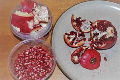 A pomegranate is shown in sections with the blossom end removed, & another in bowls of seeds & peel.