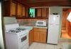 The compact kitchen comes with a 4 burner stove, refrigerator and microwave. Note the corner alcove has a back light.