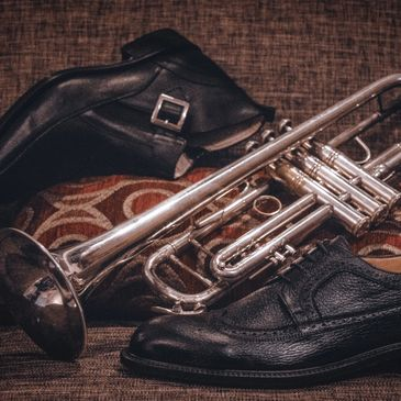 Men's shoes and trumpet image.