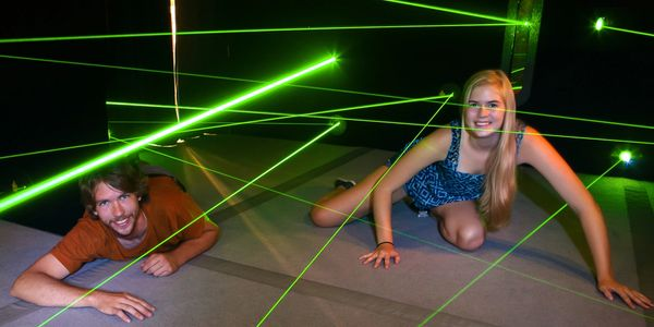 Two adults playing in Laser Maze