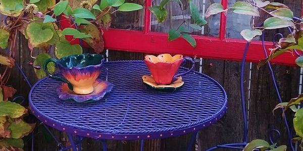 Two purple and orange pottery tea cups sitting on a purple miniature French style  table with chairs. A red framed window sits behind the tea set with a clematis growing up the side. All this hanging on a fence.
