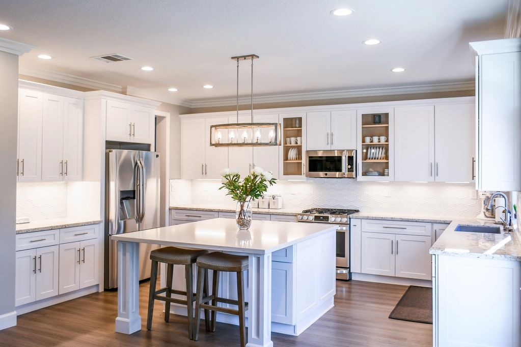 Bright white kitchen with white granite counters and a large center island.