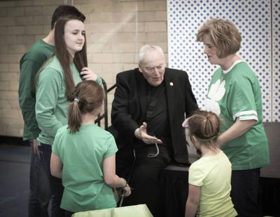 Rev, John P. Smyth holding his had out to children dressed for St. Patricks Day.