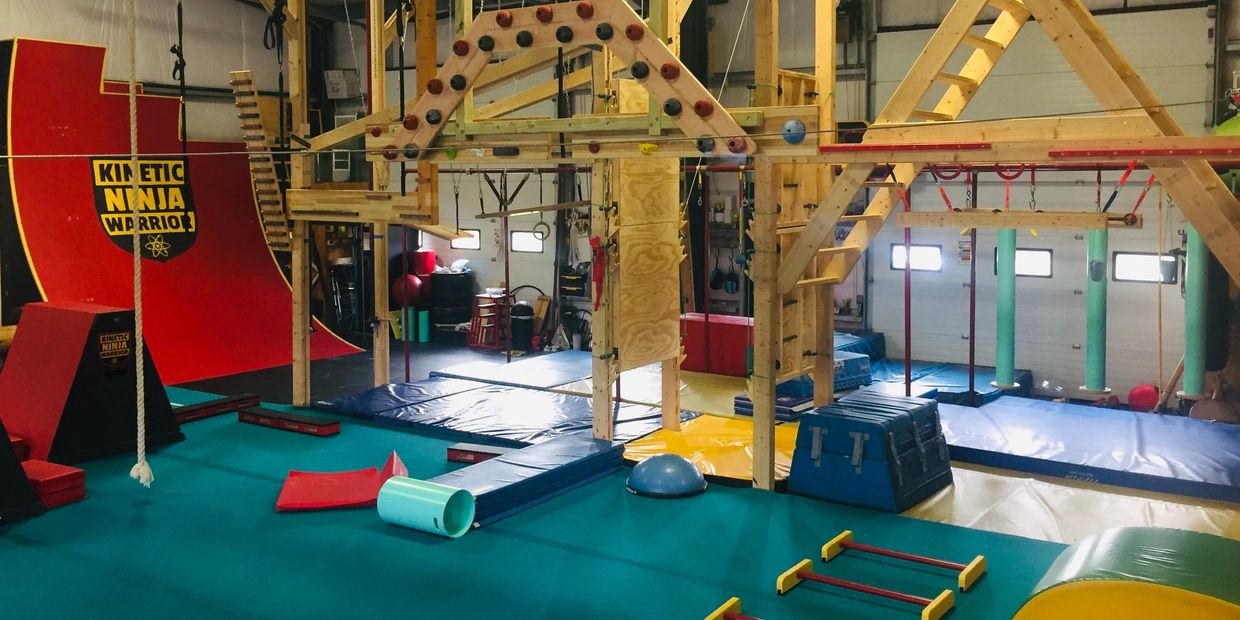Kinetic Ninja Warrior's climbing gym with warped wall, rope climb, salmon ladder, and devil steps.