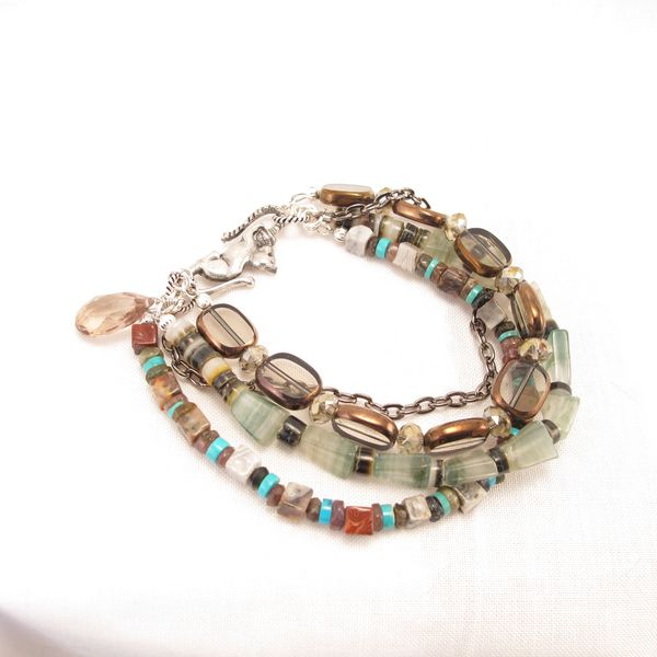 Bracelet, four strands of glass beads and gemstones.  Cat Clasp and briolette dangle