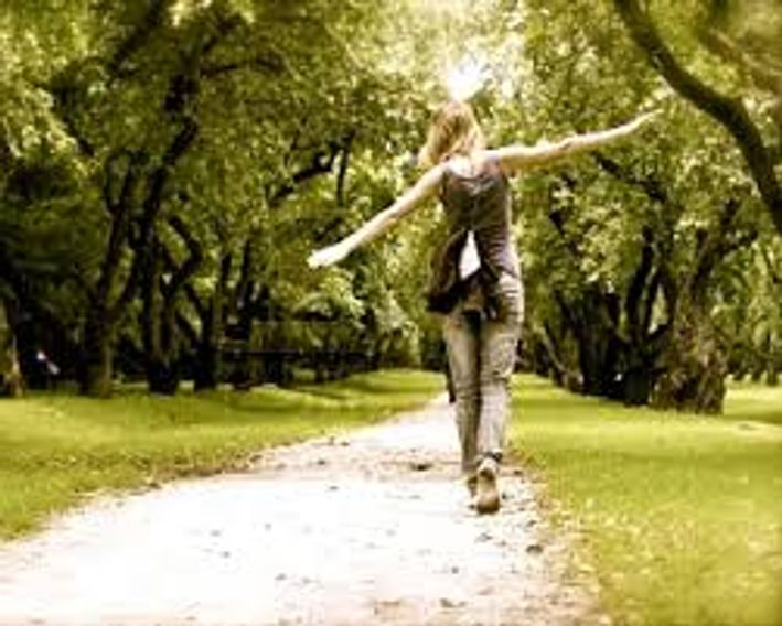 Young woman walking down a sunny footpath, with trees lining both sides