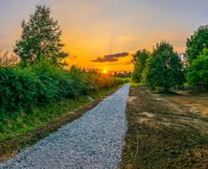 Gravel-filled footpath with greenery on either side, and a brilliant sunset in the background