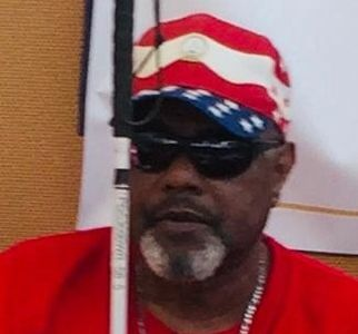 photo of male holding white can. Male wearing red shirt and red, white , blue ball cap