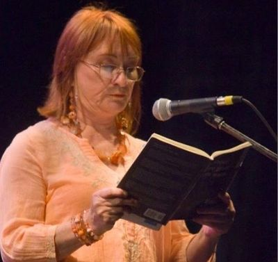 Portrait of Eileen reading from one of her books