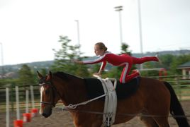 This picture is of a young girl vaulting on horseback, performing the flag, a compulsory movement.