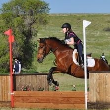 Young eventing student on course over the first fence.
