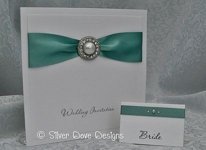 Wedding invitation with satin ribbon and large pearl and diamante embellishment. Matching place card