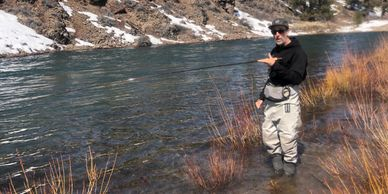 Man standing in waders with fly rod in hand on Truckee river