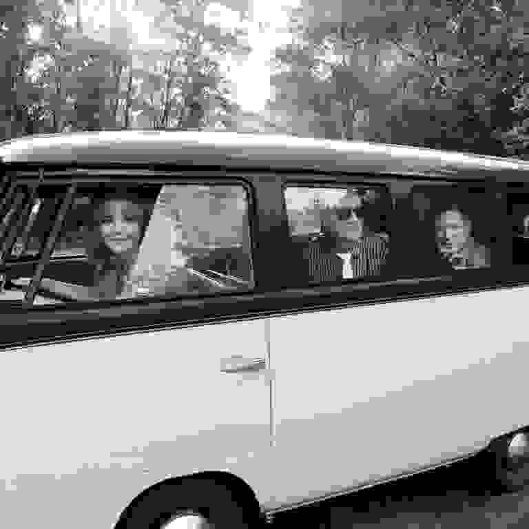 1960's VW bus with three bandmates looking out windows.