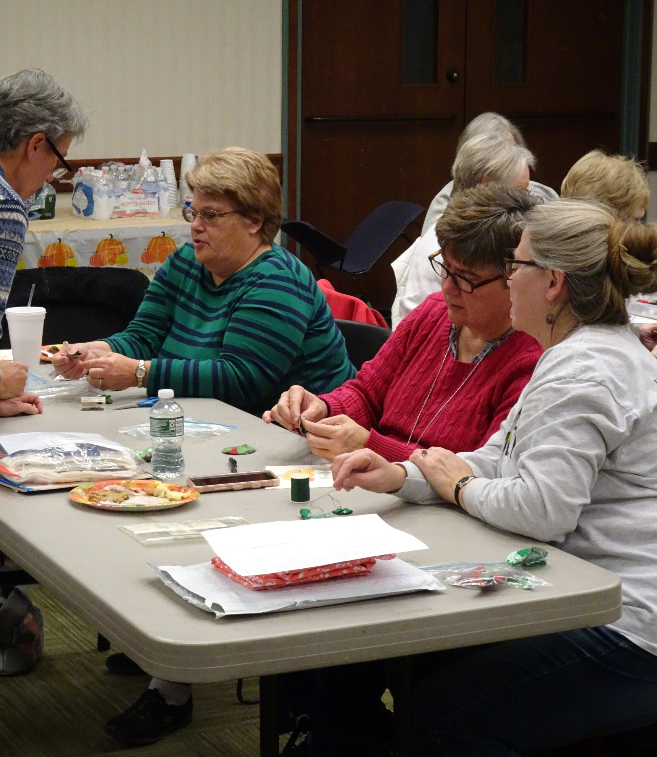 November meeting, members helping each other to work on Christmas ornaments.