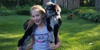 Older trained poodle puppy on young girl's shoulders being carried in the yard.