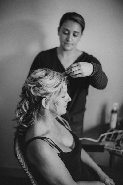 hairstylist applying the final touches to bride's hair
