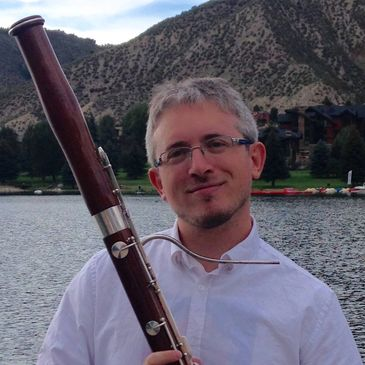 Daniel Nester holding his bassoon in the beautiful mountains