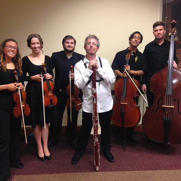 Daniel Nester holding his bassoon with members of the Kent/Blossom music festival