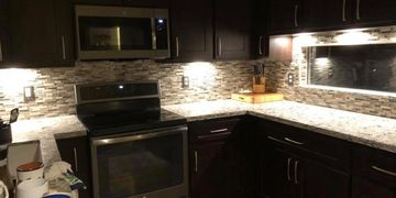 Under cabinet lighting with recessed puck lights.