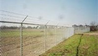 Six foot tall commercial grade chain link fence in Austin with 3 strands of barbed wire on  top