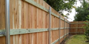 "Three rail privacy fence using 2 3/8"" galvanized steel posts and 4"" wide cedar pickets in Austin"