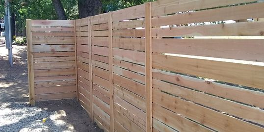"Fence installation in Austin done by alternating 6"" cedar planks with 4"" cedar planks"