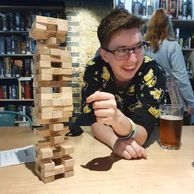 A white person with glasses and brown hair smiles while about to remove a Jenga piece.