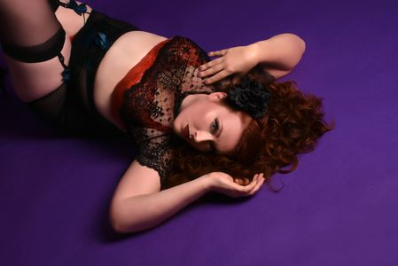 a pale woman with red hair lays on a purple backdrop, arms above her head, wearing lacy lingerie.