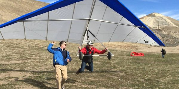 An instructor guides a hang gliding student in for a soft landing at the point of the mountain near Salt Lake City Utah