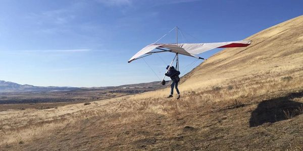 A student learning to hang glide at the Southside point of the mountain near Salt Lake City Utah