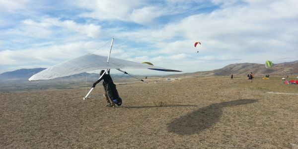 A hang glider preparing to fly with paragliders in the background at the southside of the point of the mountain near Salt Lake City Utah.