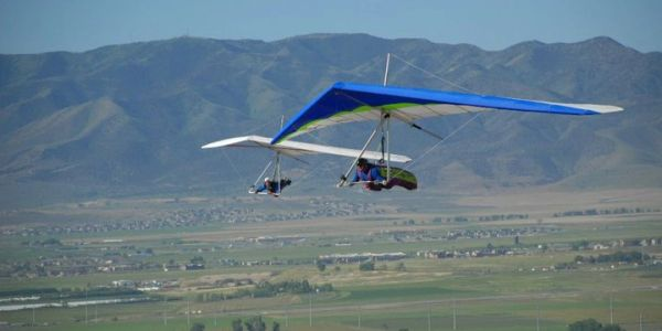 Two hang gliders flying near each other over the Salt Lake valley