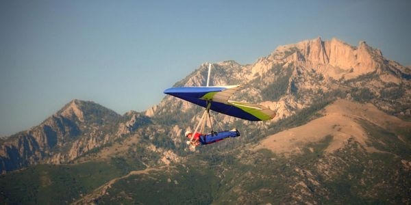 A hang glider with lone peak in the background