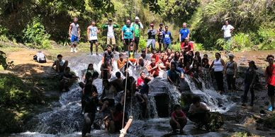 Youth and families cooling off after a hike to Tinago Falls.